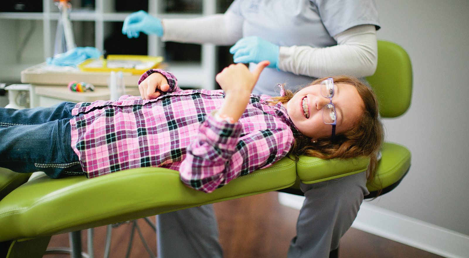 Girl smiling with braces in an orthodontic chair